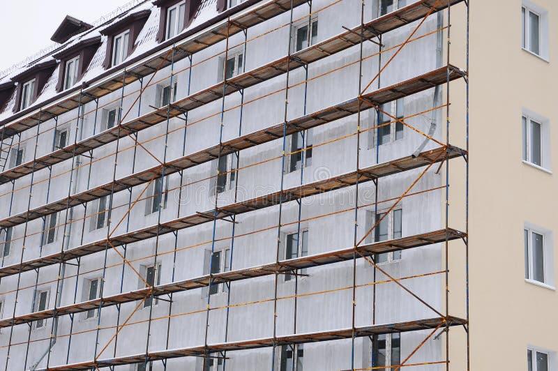 Detaljrenovering av huset med materialet till byggnadsställning Rekonstruktion av gammal byggnad arkivfoto