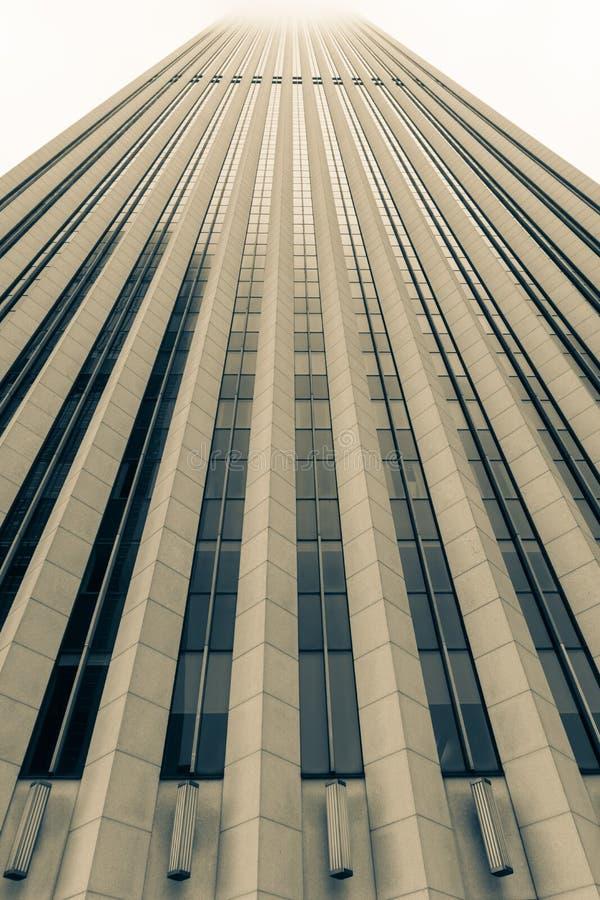 Detalle arquitectónico del rascacielos que sube en el cielo brumoso arriba, fotografía de archivo