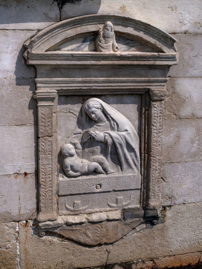 Detalle arquitectónico - una escultura del bajorrelieve de la Virgen María con el bebé Jesús Venecia, Italia El bajorrelieve es fotos de archivo