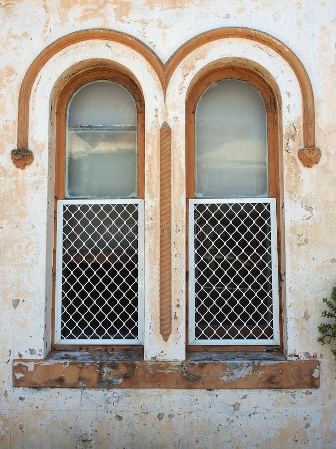 Detalle arquitectónico, Windows arqueado gemelo en el edificio viejo fotografía de archivo