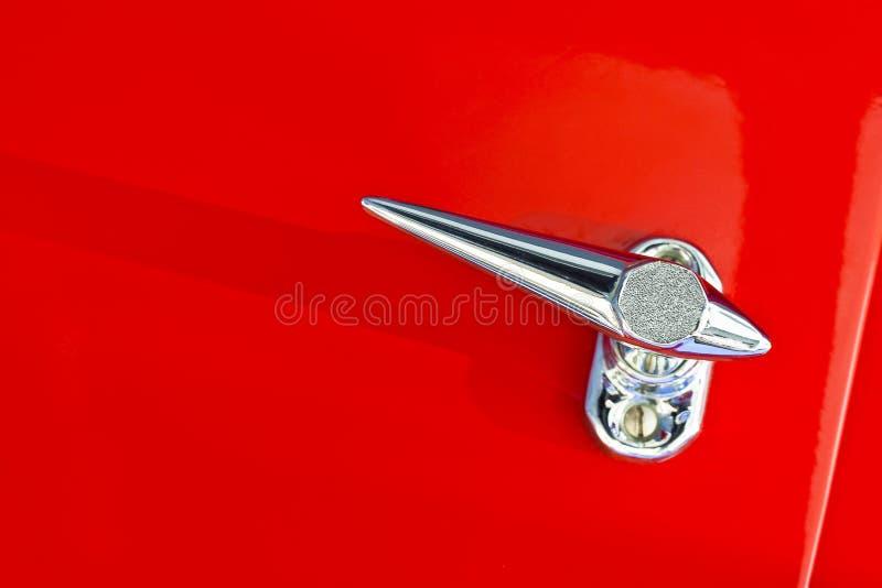 Detalle cromado de la manija en fondo rojo de un coche de deportes del vintage foto de archivo libre de regalías