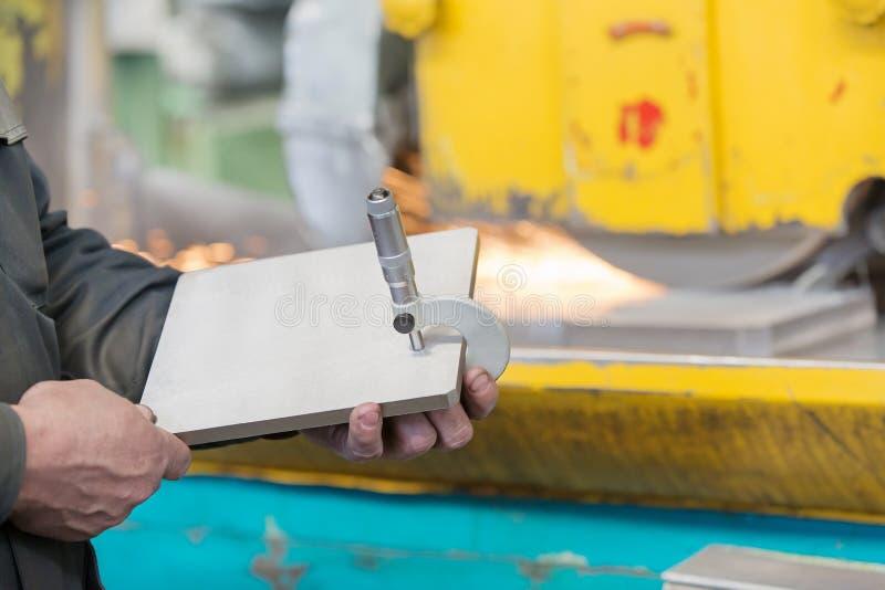 Detalle de acero de la medida del trabajador del taller de la fábrica con la herramienta del micrómetro del calibrador fotografía de archivo libre de regalías