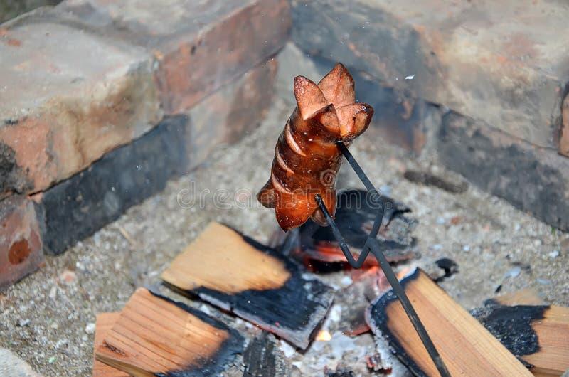 Detalle de asar a la parrilla la salchicha sobre un fuego en verano foto de archivo libre de regalías