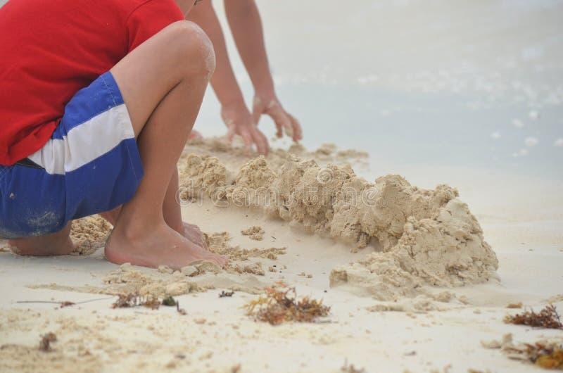 Detalle de dos niños que construyen un castillo de la arena y que juegan con la arena en una playa imagen de archivo