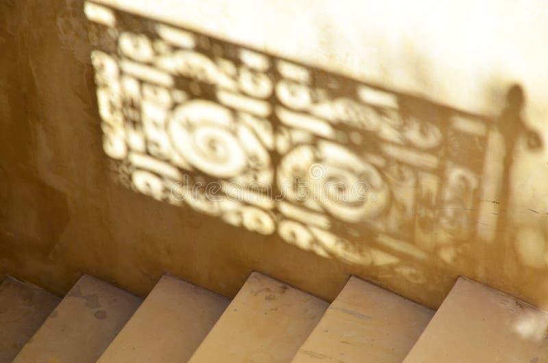 Detalle de escaleras con la reflexión de una barandilla adornada que sombrea en la pared fotos de archivo