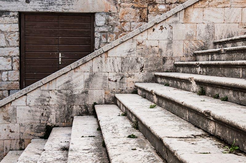 Detalle de la calle con las escaleras de piedra y puerta de madera de la iglesia en la ciudad de la fuerza, Croacia foto de archivo libre de regalías