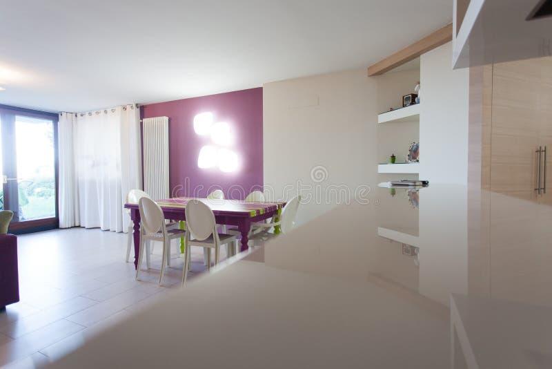 Detalle de la cocina y del sitio dinning con la tabla y las sillas coloridas imagen de archivo