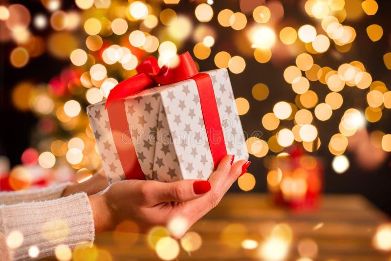 Detalle de la mano de la mujer que sostiene el regalo de la Navidad con el punto ligero de la falta de definición imagenes de archivo