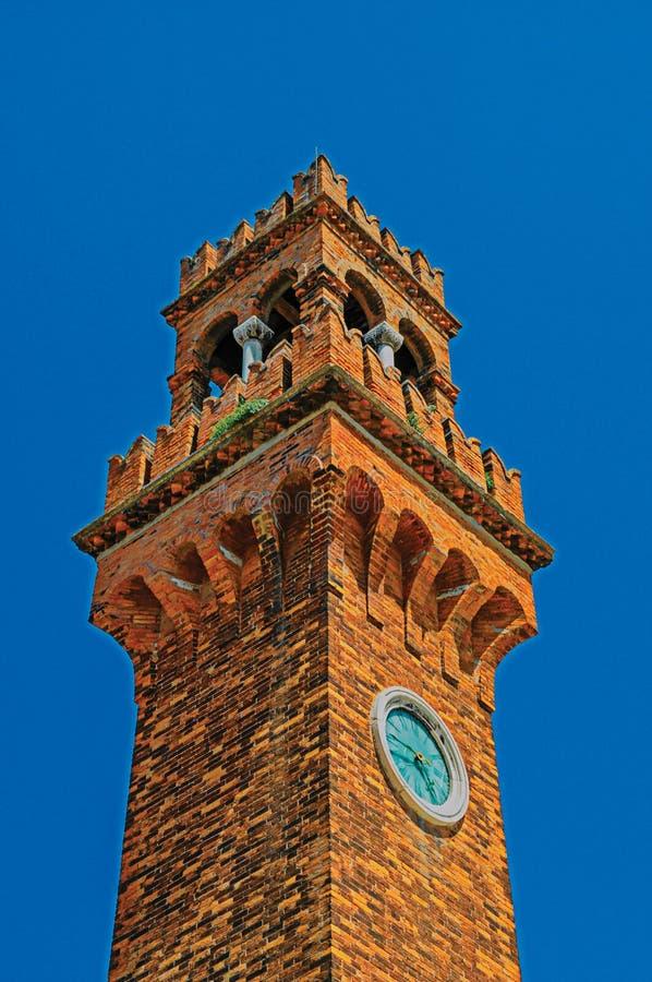 Detalle de la torre de reloj hecho de ladrillos con el cielo azul soleado en Murano foto de archivo