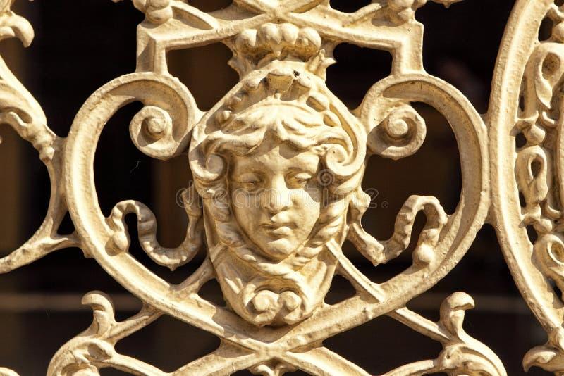 Detalle de la verja histórica del metal con la cara de la muchacha imagen de archivo