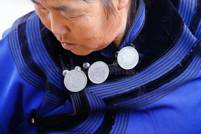 Detalle de las decoraciones de un vestido de la mujer s en un pueblo en Yunnan meridional, China Yunnan, China imagen de archivo