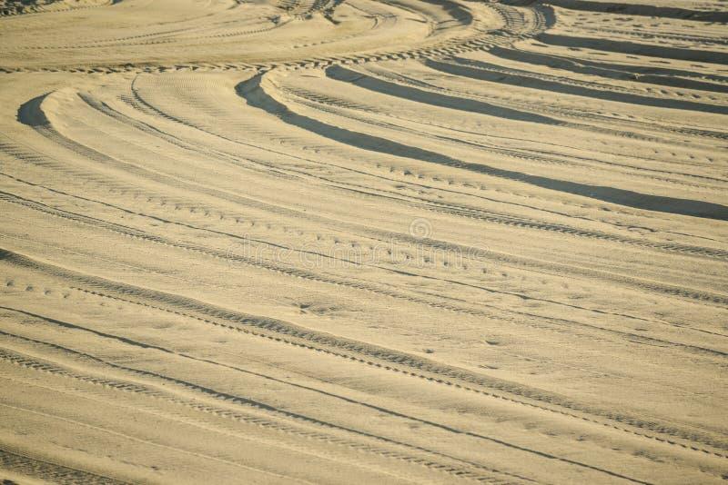 Detalle de las pistas del neum?tico en desierto de la arena imagenes de archivo