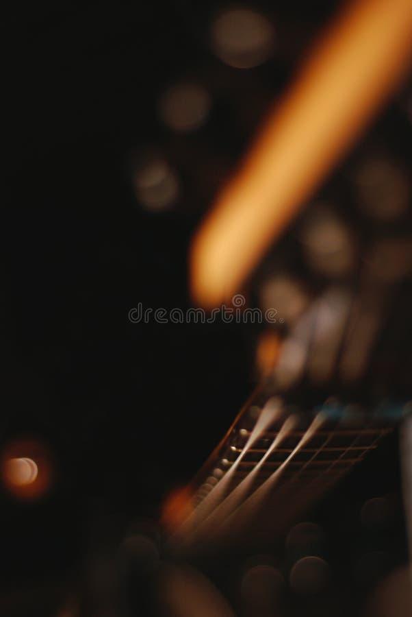 Detalle de las secuencias de la guitarra con el fondo caliente borroso imagen de archivo libre de regalías