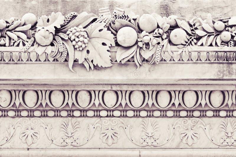 Detalle de los aleros italianos viejos de una piedra del moldeado con las flores y el franco fotos de archivo libres de regalías