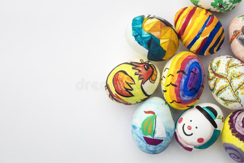 Detalle de los huevos de Pascua pintados con diversas formas, las historietas y los colores brillantes en el fondo blanco foto de archivo libre de regalías
