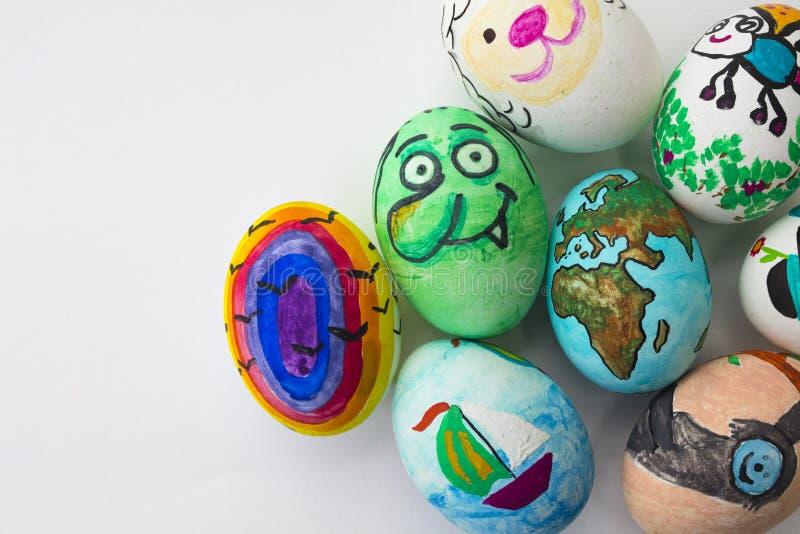 Detalle de los huevos de Pascua pintados con diversas formas, las historietas y los colores brillantes en fondo blanco aislado fotos de archivo