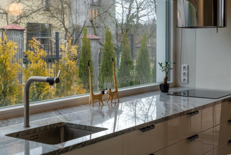 Detalle de los muebles y de la ventana elegantes de la cocina imagenes de archivo