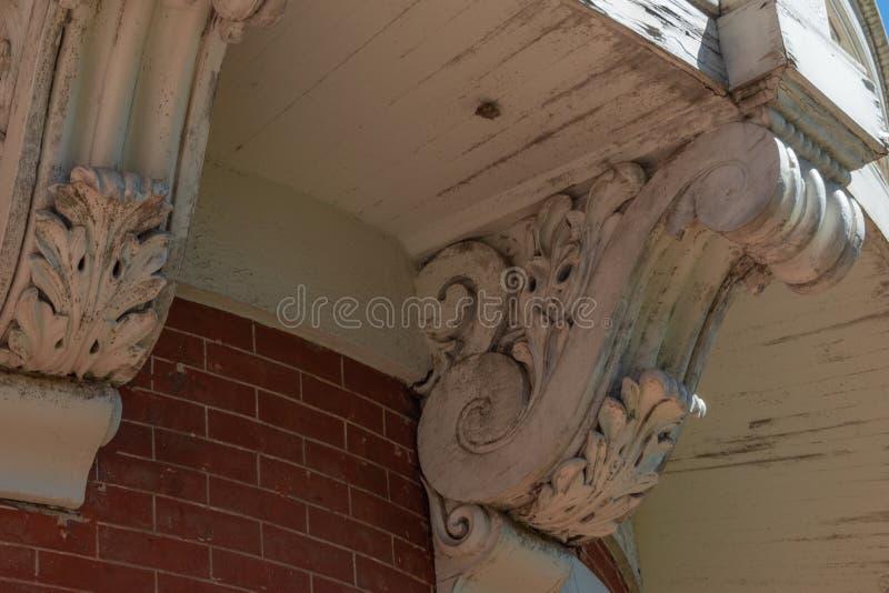Detalle de ménsulas elaboradas debajo de un balcón y de una pared de ladrillo curvados foto de archivo