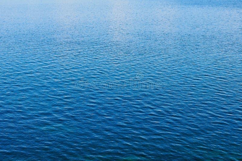 Detalle de ondulaciones múltiples en la agua de mar azul tranquila imagen de archivo libre de regalías
