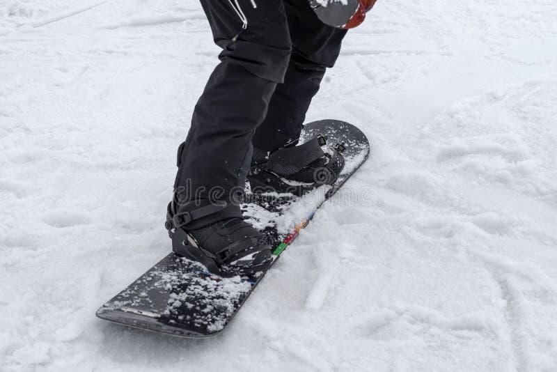 Detalle de piernas del snowboarder joven en primer de las botas Deporte de invierno, snowboard, forma de vida al aire libre del o fotografía de archivo
