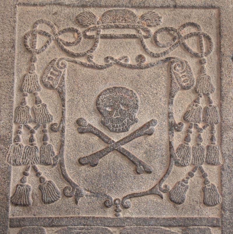Detalle de un bastidor de piedra tallado antiguo con con el cráneo y el hueso fotos de archivo