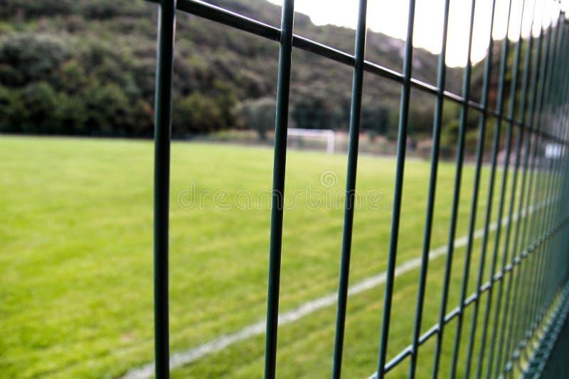 Detalle de un campo de fútbol con la línea blanca y la cerca/la cerca verde red-formada metálica ascendente cercana foto de archivo libre de regalías