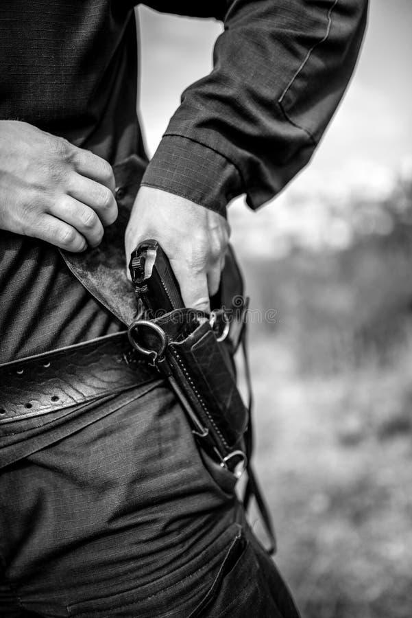 Detalle de un oficial de policía que sostiene el arma imagenes de archivo