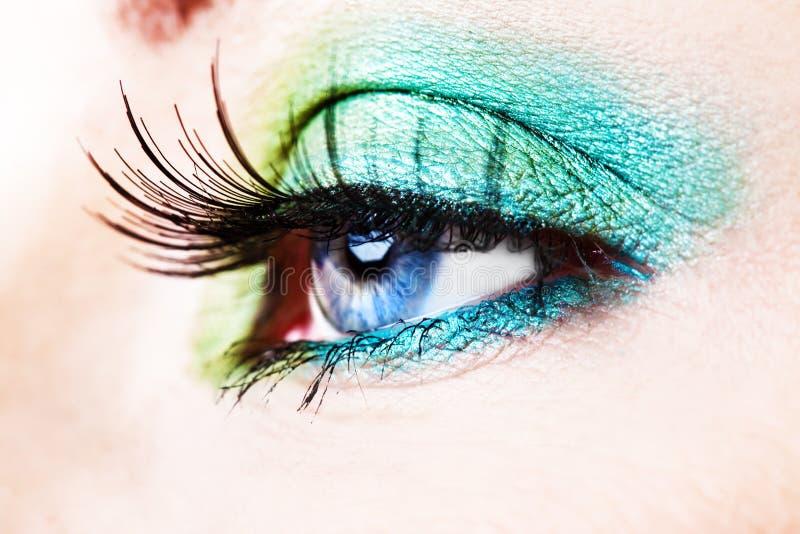 Detalle de un ojo azul con el eyeshade verde foto de archivo