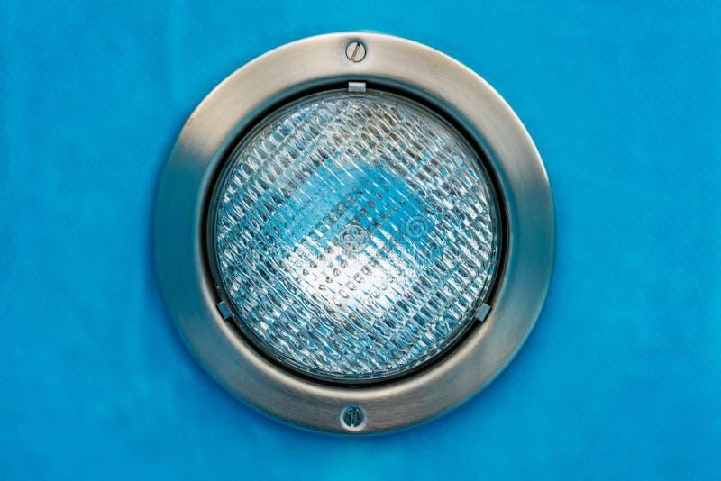 Detalle de un proyector redondo de la piscina con el fondo azul imagenes de archivo