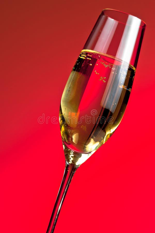 Detalle de una flauta de champán en fondo de la luz roja imagen de archivo