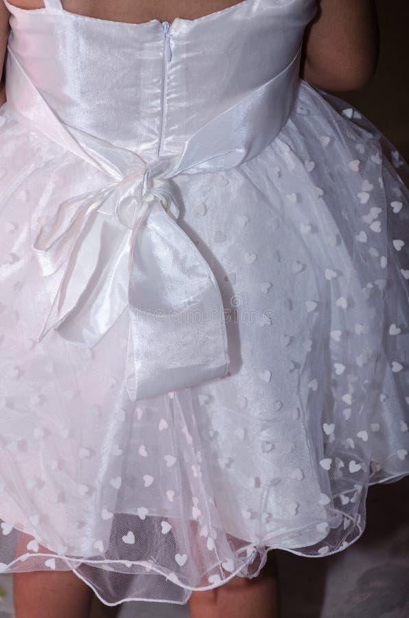 Detalle de una muchacha blanca del vestido con un arco en los corazones traseros y blancos fotos de archivo libres de regalías