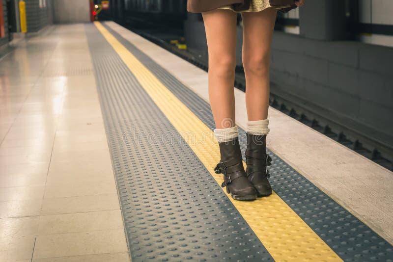 Detalle de una mujer joven hermosa que presenta en una estación de metro fotografía de archivo