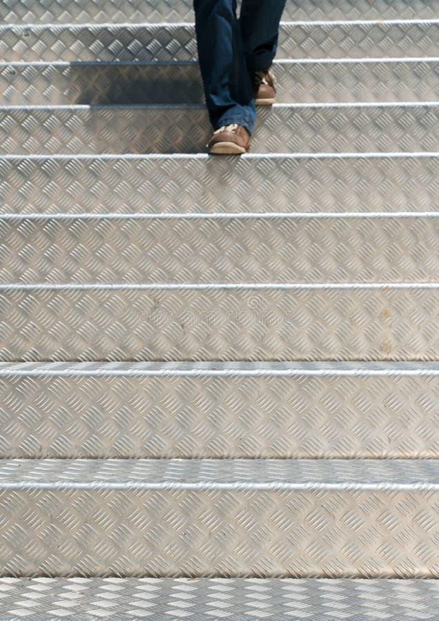 Detalle de una mujer que camina abajo de las escaleras de aluminio fotos de archivo