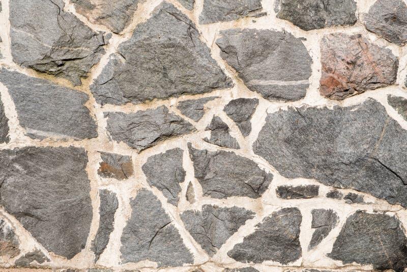 Detalle de una pared hecha de pedazos de piedra fotos de archivo