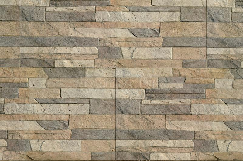 Detalle de una pared de un ladrillo gris y marrón largo La fachada del edificio, construida de piedra natural textur del fondo imagenes de archivo