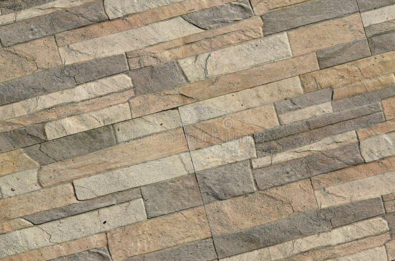 Detalle de una pared de un ladrillo gris y marrón largo La fachada del edificio, construida de piedra natural textur del fondo fotografía de archivo libre de regalías