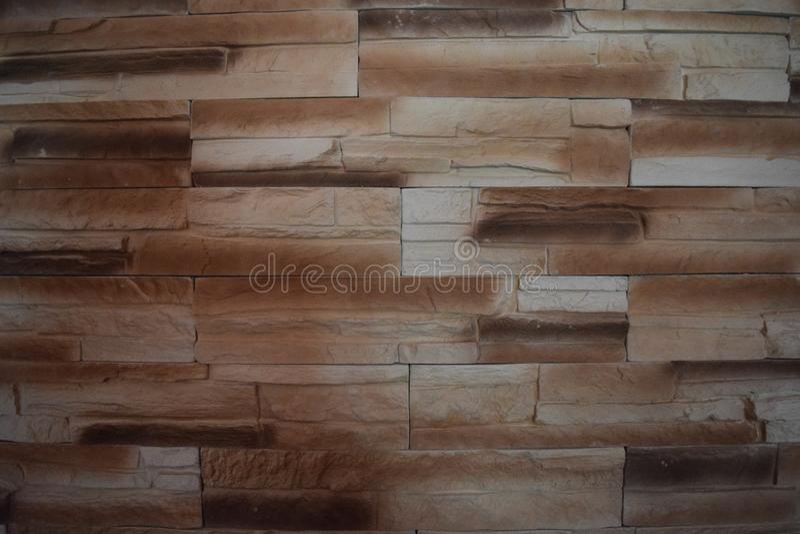 Detalle de una pared de un ladrillo gris y marrón largo La fachada del edificio, construida de piedra natural textur del fondo de fotografía de archivo libre de regalías