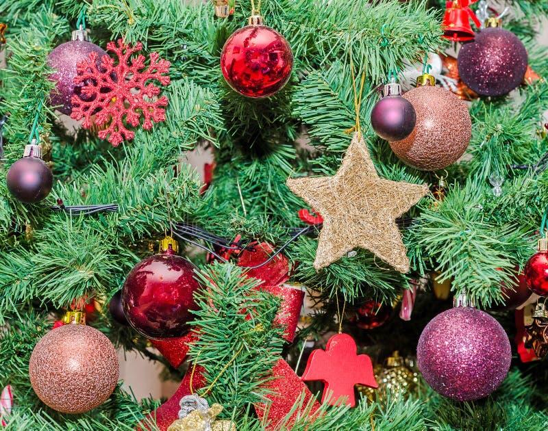 Detalle del árbol verde de la Navidad (Chrismas) con los ornamentos coloreados, globos, estrellas, Santa Claus, muñeco de nieve imagen de archivo