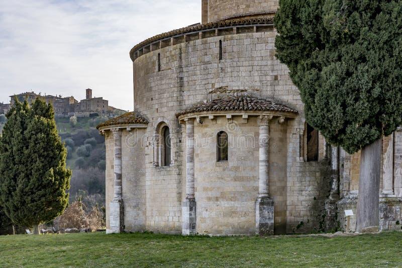 Detalle del ábside del Sant 'Antimo Abbey con en el fondo que el pueblo del dell de Castelnuovo 'reduce, Siena, Toscana, Italia imagenes de archivo