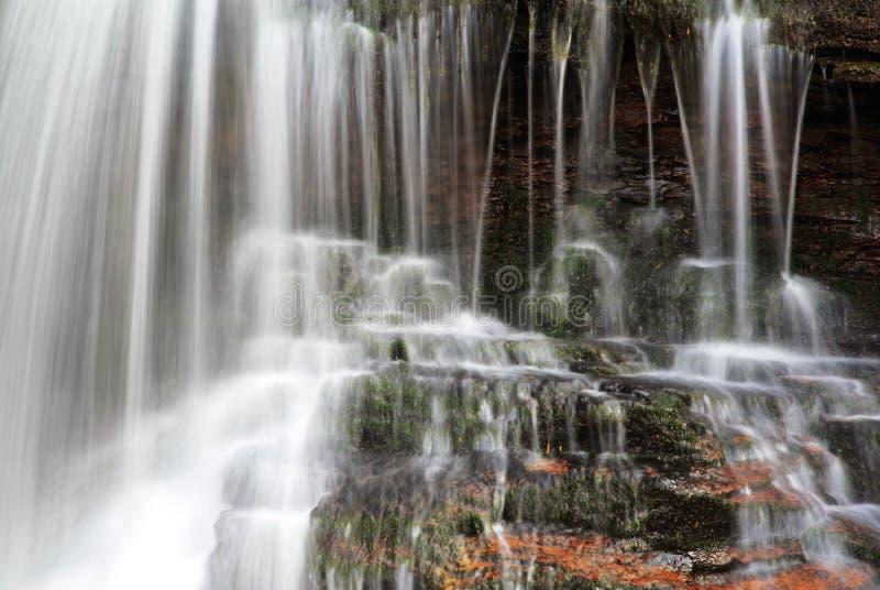 Detalle del agua borrosa que cae sobre musgo y roca roja imágenes de archivo libres de regalías