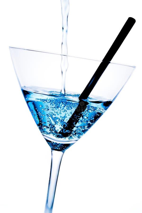 Detalle del cóctel azul con las burbujas y la paja negra imagenes de archivo