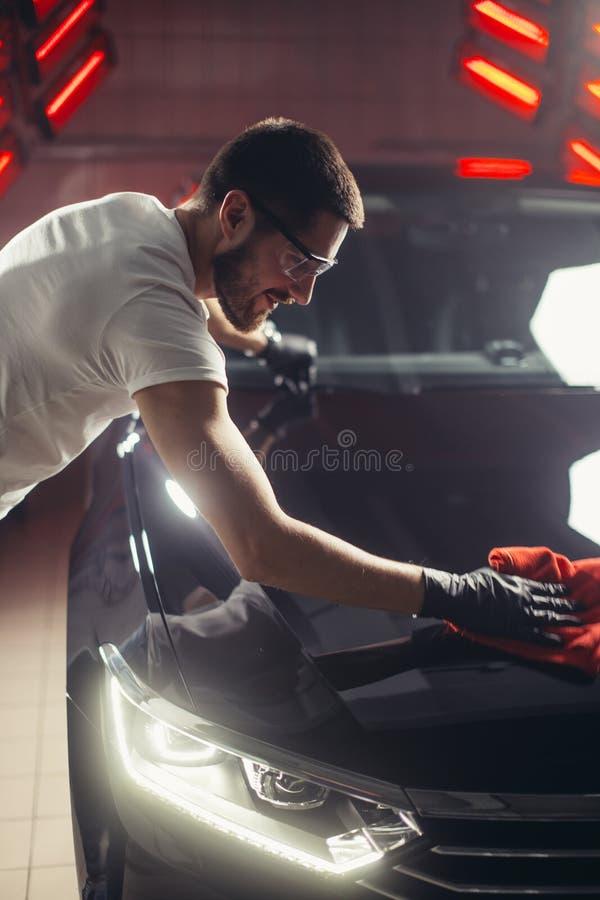 Detalle del coche - el hombre sostiene la microfibra disponible y pule el coche fotografía de archivo