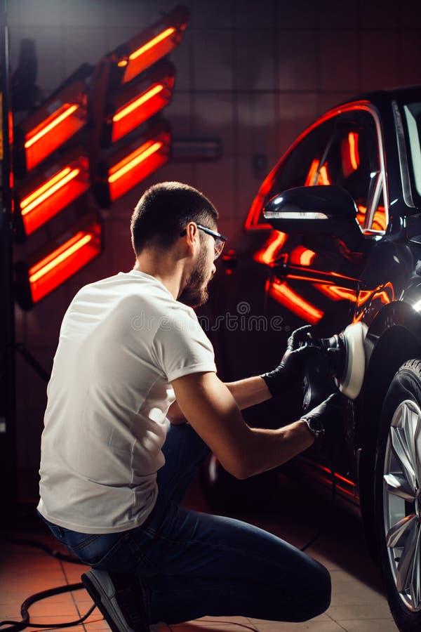 Detalle del coche - hombre con el pulidor orbital en taller de reparaciones auto Foco selectivo imagen de archivo
