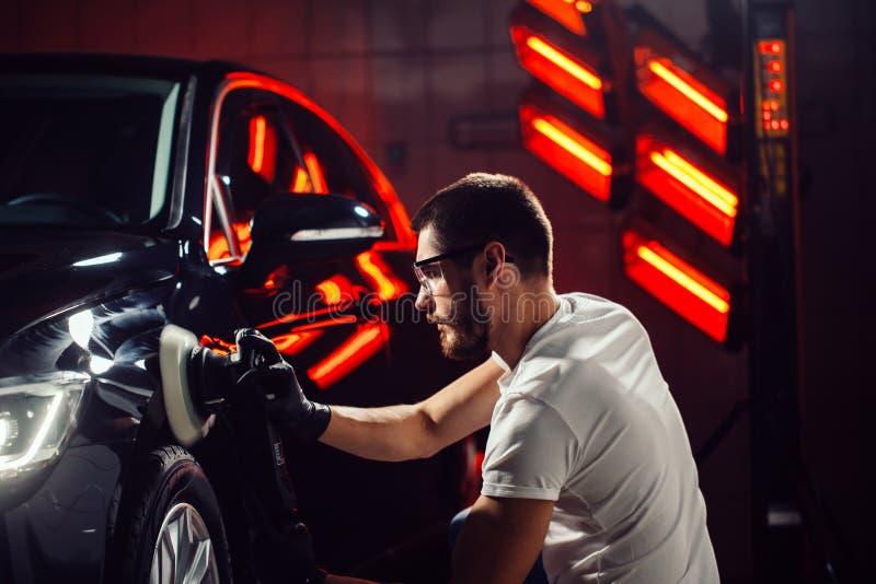 Detalle del coche - hombre con el pulidor orbital en taller de reparaciones auto Foco selectivo foto de archivo
