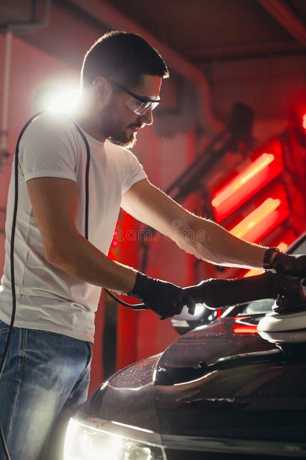 Detalle del coche - hombre con el pulidor orbital en taller de reparaciones auto Foco selectivo fotografía de archivo