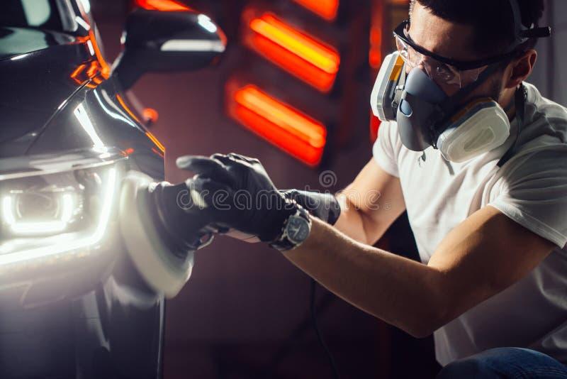 Detalle del coche - hombre con el pulidor orbital en taller de reparaciones auto Foco selectivo fotos de archivo