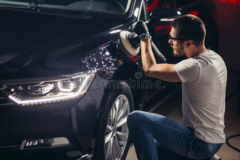 Detalle del coche - hombre con el pulidor orbital en taller de reparaciones auto Foco selectivo imágenes de archivo libres de regalías