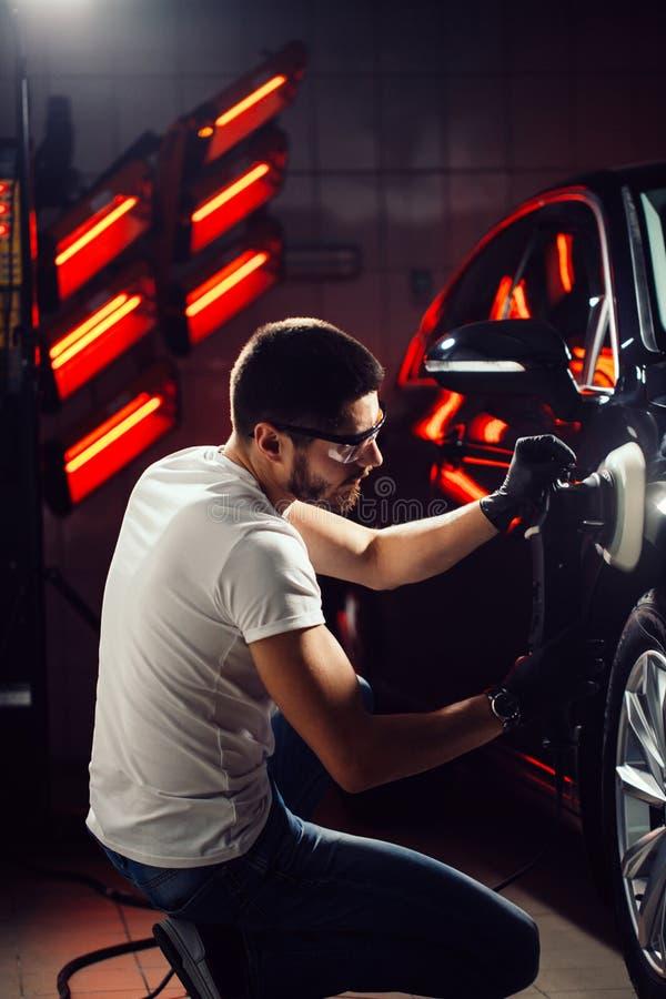Detalle del coche - hombre con el pulidor orbital en taller de reparaciones auto Foco selectivo imagen de archivo libre de regalías