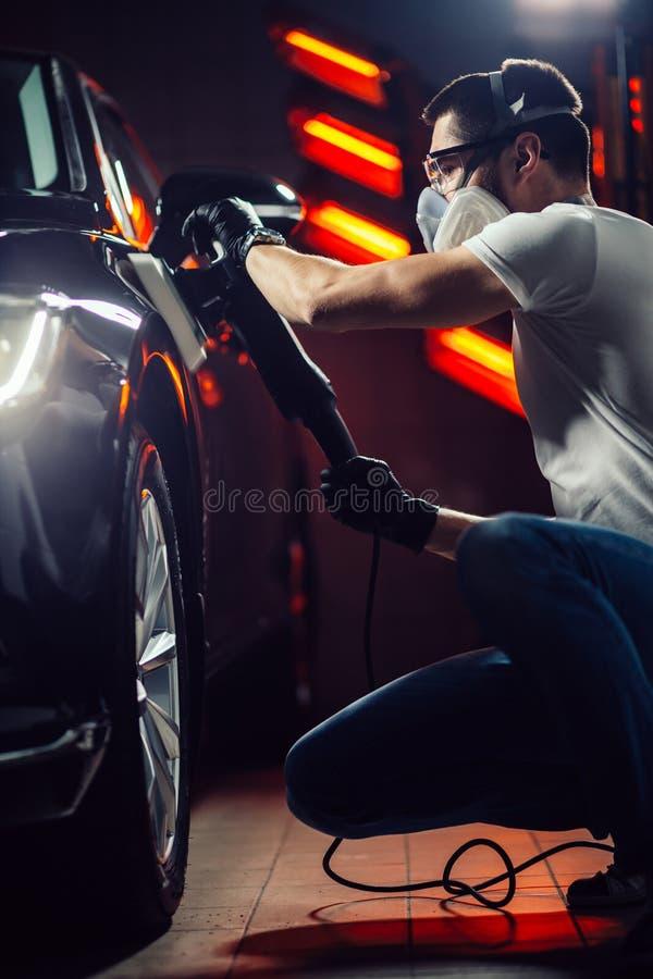 Detalle del coche - hombre con el pulidor orbital en taller de reparaciones auto Foco selectivo imagenes de archivo