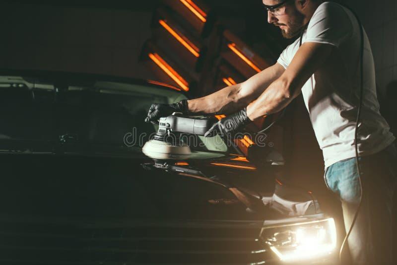 Detalle del coche - hombre con el pulidor orbital en taller de reparaciones auto Foco selectivo fotografía de archivo libre de regalías